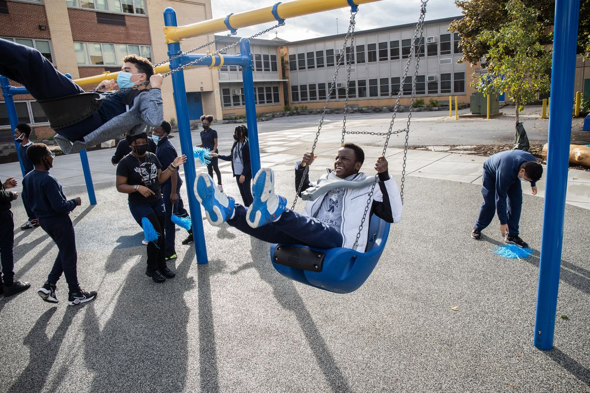 """Kevin Edouard swings on Arnold Mireles Academy's new """"Space to Grow"""" schoolyard in the South Chicago neighborhood."""