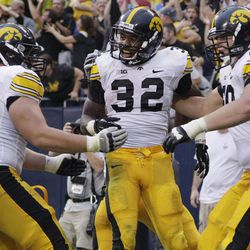 Iowa running back Andre Dawson (32) celebrates with offensive linemen Austin Blythe (63) and Matt Tobin (60) after scoring a touchdown during the second half of an NCAA college football game against Northern Illinois at Soldier Field in Chicago, Saturday, Sept. 1, 2012. Iowa won 18-17.