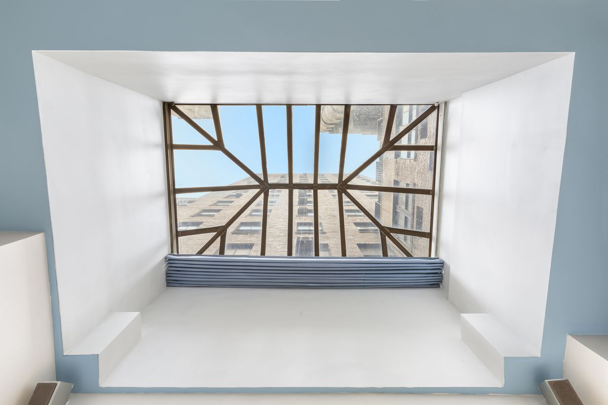 A white and blue ceiling surrounding a skylight.