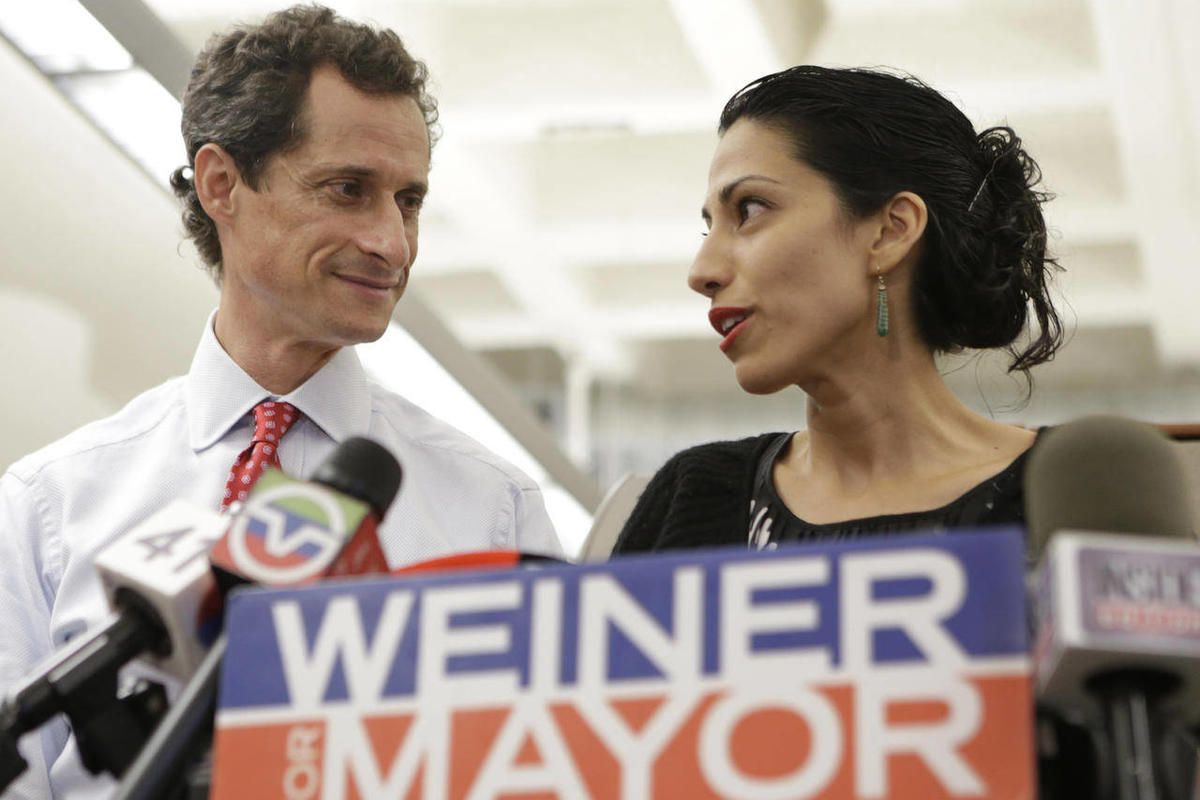 """In this July 23, 2013 photo, Huma Abedin, alongside her husband, New York mayoral candidate Anthony Weiner, speaks during a news conference at the Gay Men's Health Crisis headquarters in New York. When Abedin""""™s name and face first started appearing in th"""