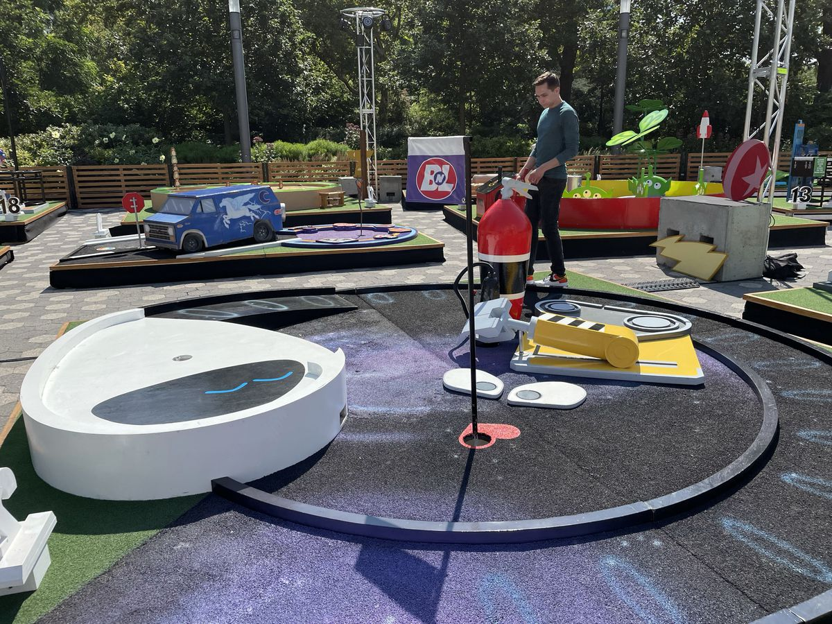 a circular minigolf course designed to look like Pixar's WALL-E; Austen stands next to it