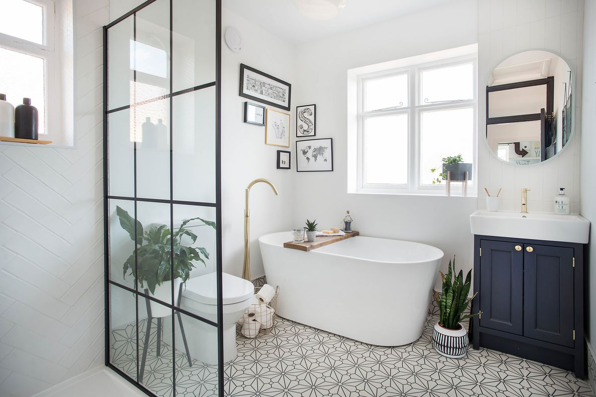 A modern bathroom with stand alone tub, glass shower door and patterned ceramic tiles.