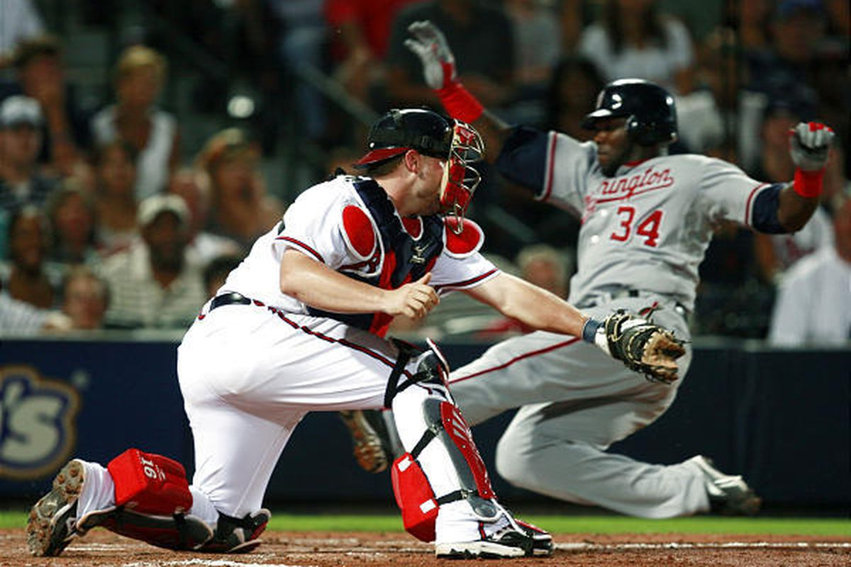Washington Nationals' Elijah Dukes (34) scores on a Ronnie Belliard base hit as Atlanta Braves catcher Brian McCann applies the late tag.