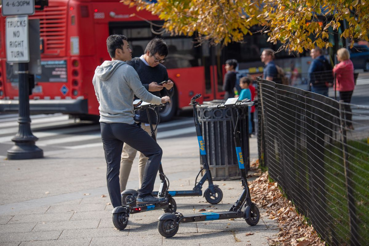 Two men standing near three Skip scooters in D.C. during the fall. An adjacent tree has turning leaves and there is a Metro bus in the background.