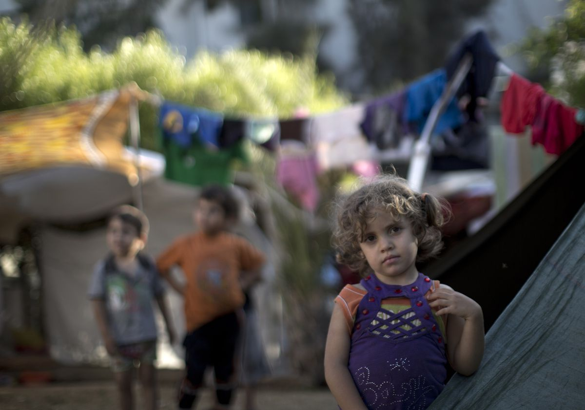 A displaced Palestinian girl stands next to a makeshift tent at the al-Shifa hospital in Gaza City where many Palestinians have have taken refuge after fleeing attacks in the Shejaiya neighbourhood of the city. Mahmud Hams/AFP/Getty Images