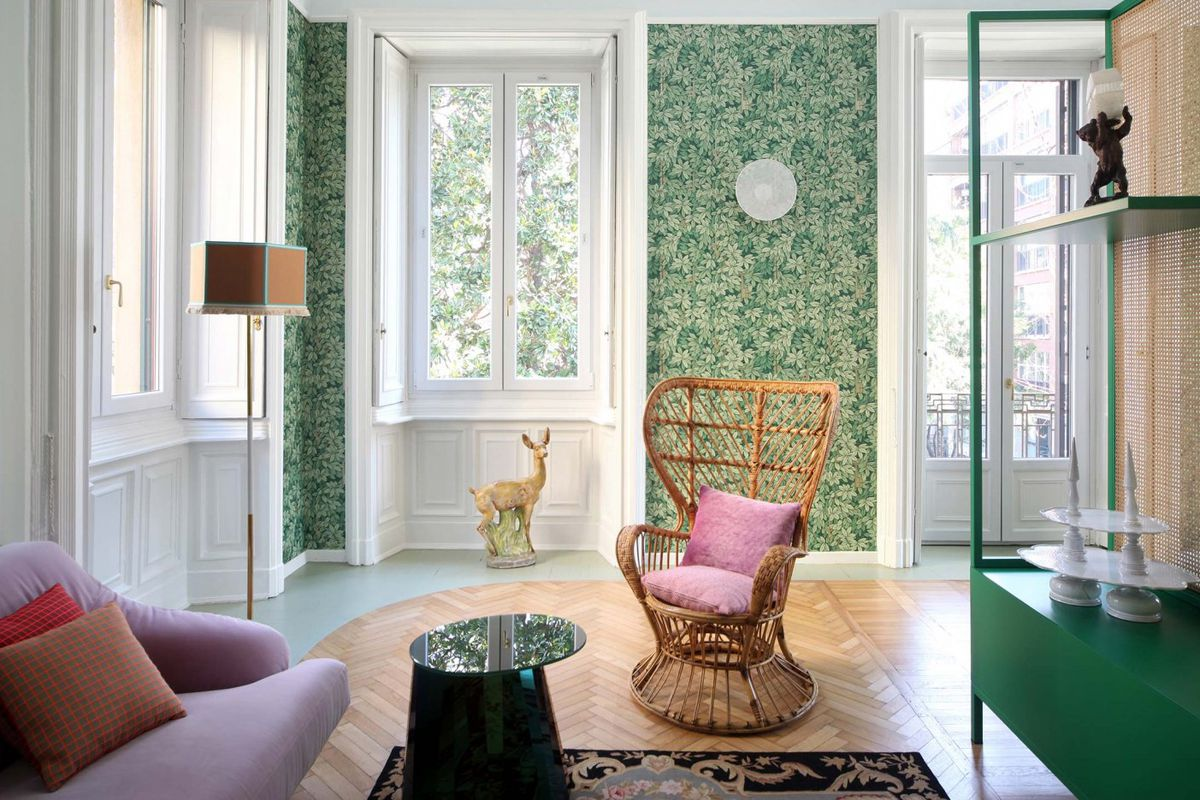 Living area with French doors, green foliage-patterned wallpaper, herringbone wood floors, and decorated with whicker chair, pink sofa, and other retro-contemporary pieces.