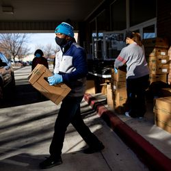 Al Noble carries a box of food to a car at Calvary Baptist Church in Salt Lake City on Saturday, Dec. 19, 2020.