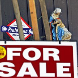 """A religious statuette is displayed with a """"For Sale"""" sign on the front porch of the home of Nakoula Basseley Nakoula, the man who made the film """"Innocence of Muslims"""" that has sparked violent protests, on a street in Cerritos, Calif., Tuesday, Sept. 25, 2012. The filmmaker has received death threats and was forced into hiding after the 14-minute movie trailer rose to prominence."""