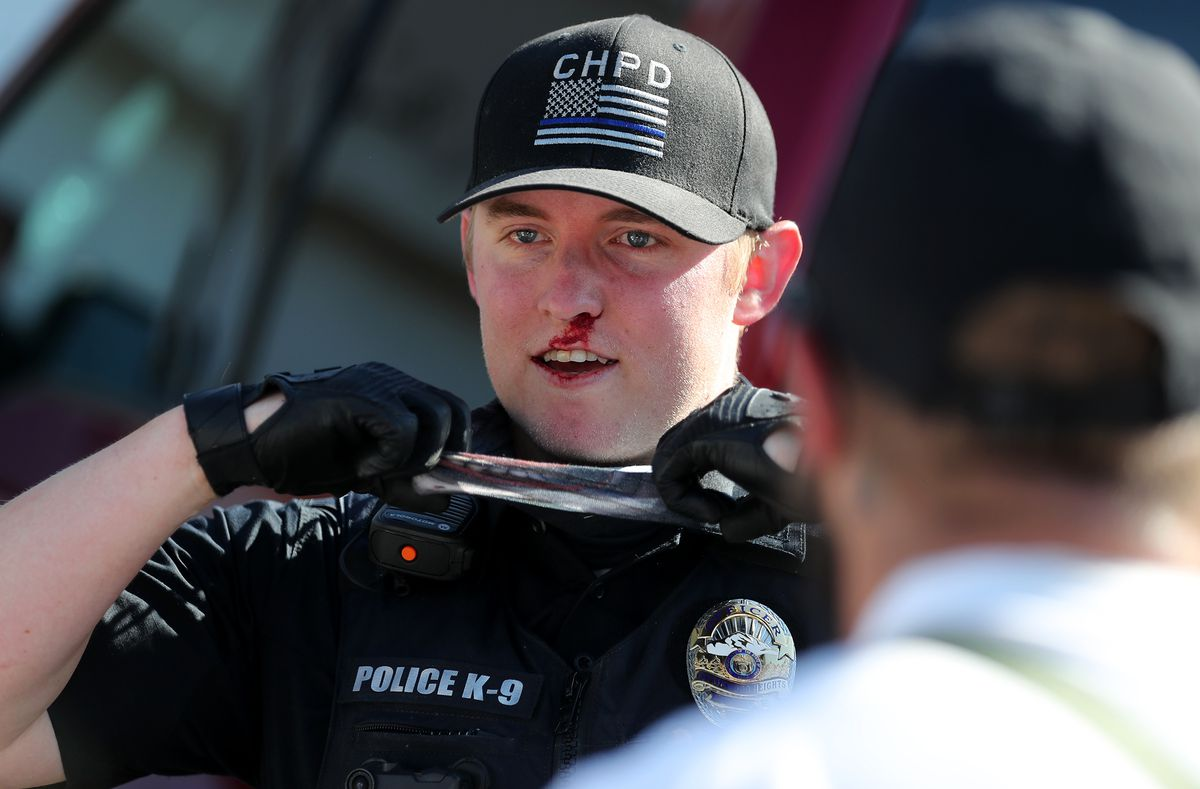 An officer with a bloody nose puts his mask back on after police and marchers collided in the streets of Cottonwood Heights on Sunday, Aug. 2, 2020. The group was marching on 6710 South when police blocked them at Cristobal Street and a confrontation ensued. Police said eight or nine protesters were arrested.