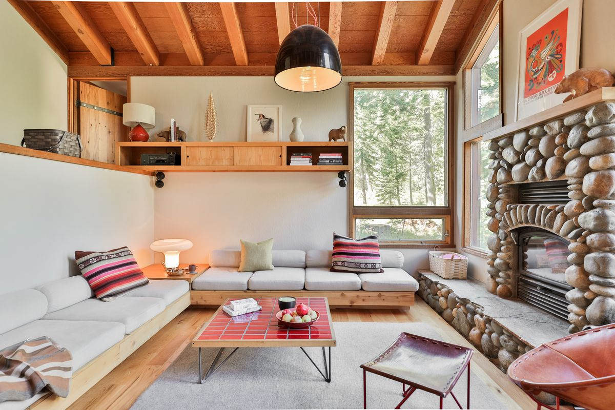 A room with a stone fireplace, white walls, L-shaped couch, and a coffee table with red tile on top.