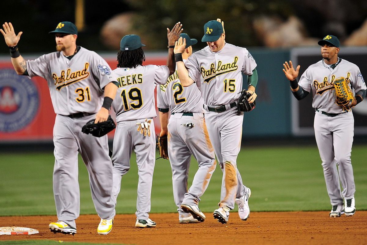 April 18, 2012; Anaheim, CA, USA; Oakland Athletics celebrate their 6-0 victory against the Los Angeles Angels at Angel Stadium. Mandatory Credit: Gary A. Vasquez-US PRESSWIRE
