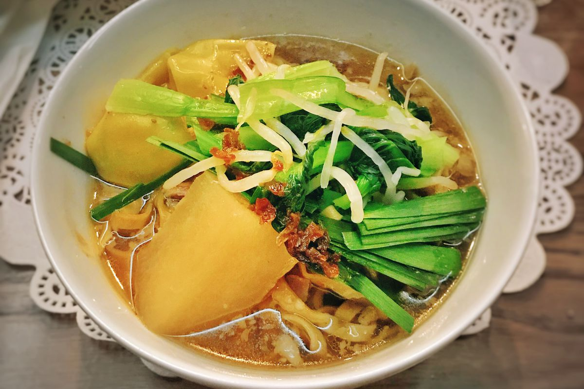 A blue bowl holds Phnom Penh noodles at Sunshine, filled with an orange liquid, squash, and greens, with cut-up chiles and bean sprouts.
