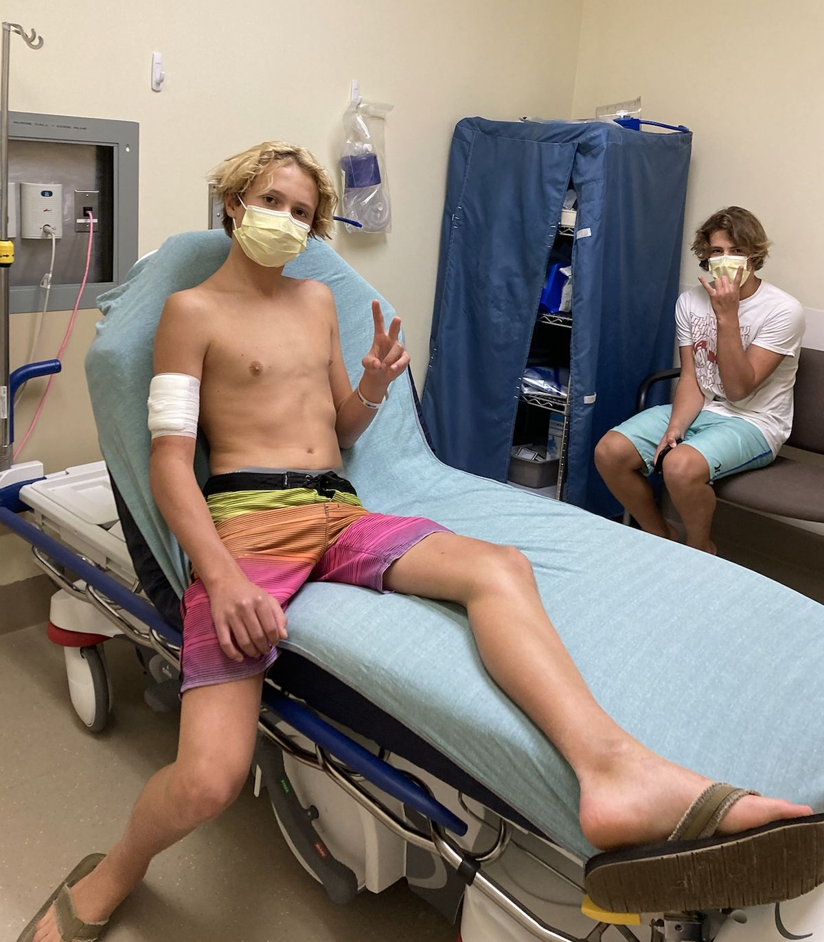 Teen surfer Doyle Nielsen receives treatment at a hospital in Florida following a shark attack on Sept. 9, with his brother Logan nearby.