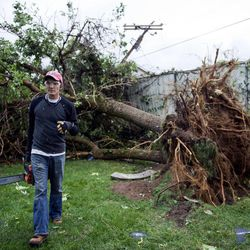 Blake Isaacson walks with his chainsaw in hand to help neighbors remove fallen trees after a tornado struck Washington Terrace on Thursday, Sept. 22, 2016. Officials said nobody was injured in the twister.