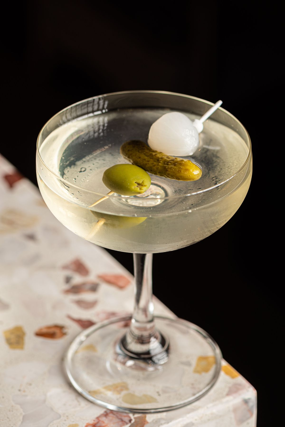 A riff on a martini in a coup glass with dill pickle brine, vodka, and olive garnishes.