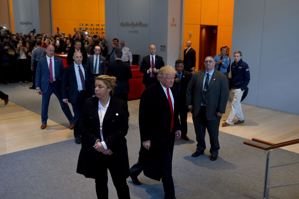 Donald Trump walking through the lobby of the New York Times building.