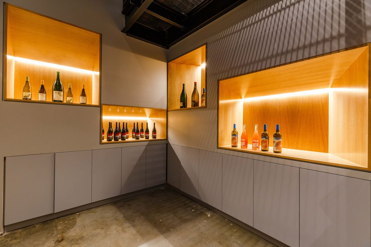 A corner of a wall shows four lit-up boxes of varying sizes, where wine collections sit.