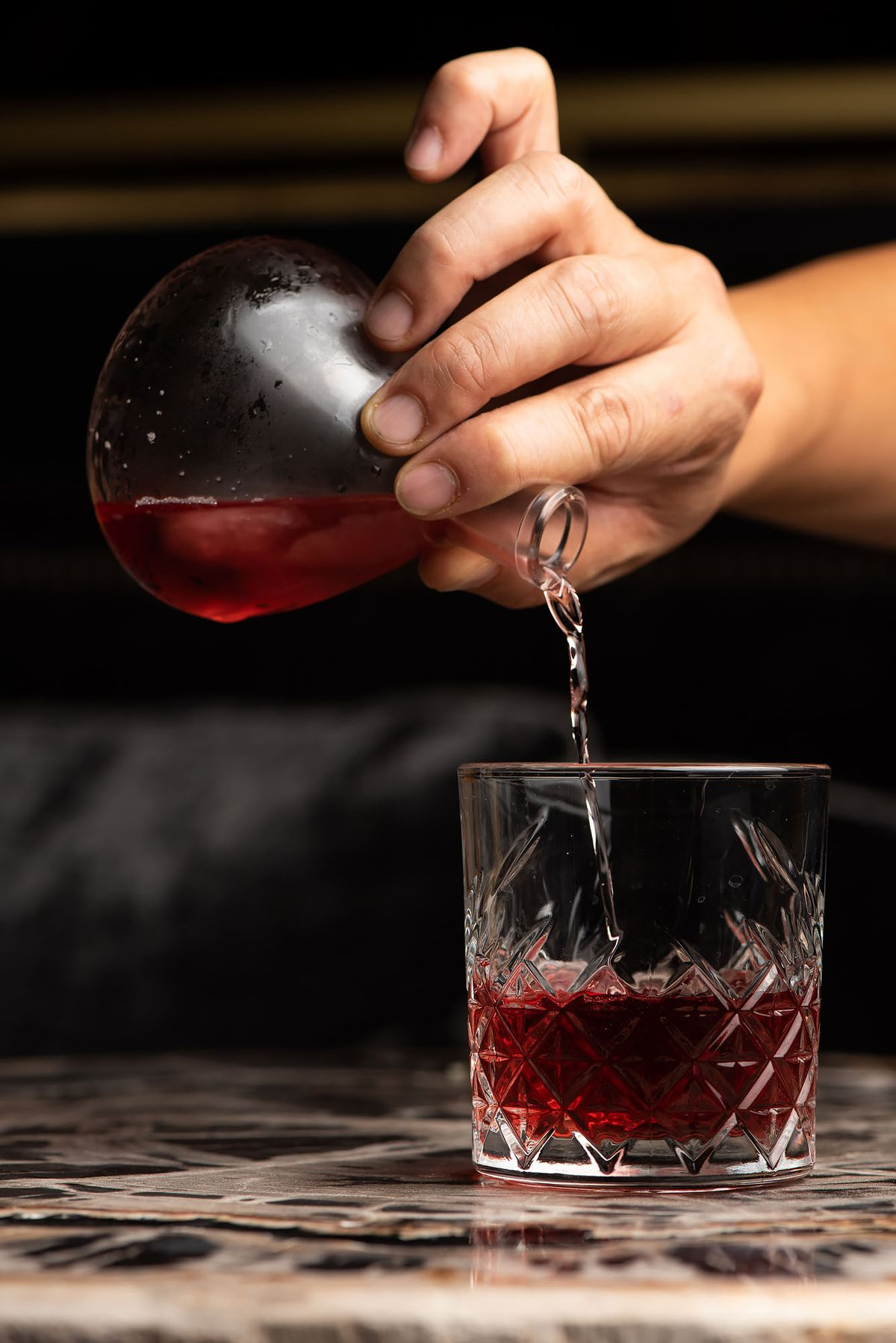 A deep red cocktail being poured into a clear glass.