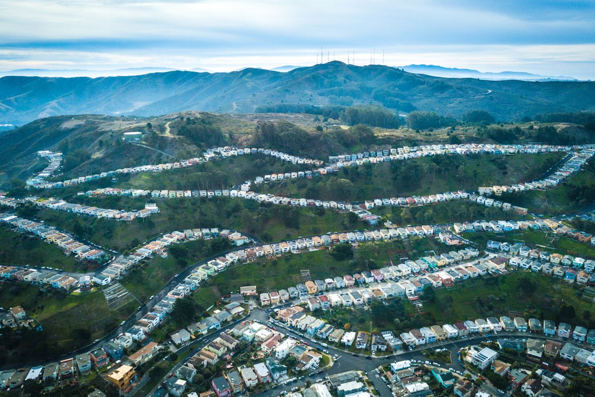 An aerial photo of tracts of homes crisscrossing a series of hills.