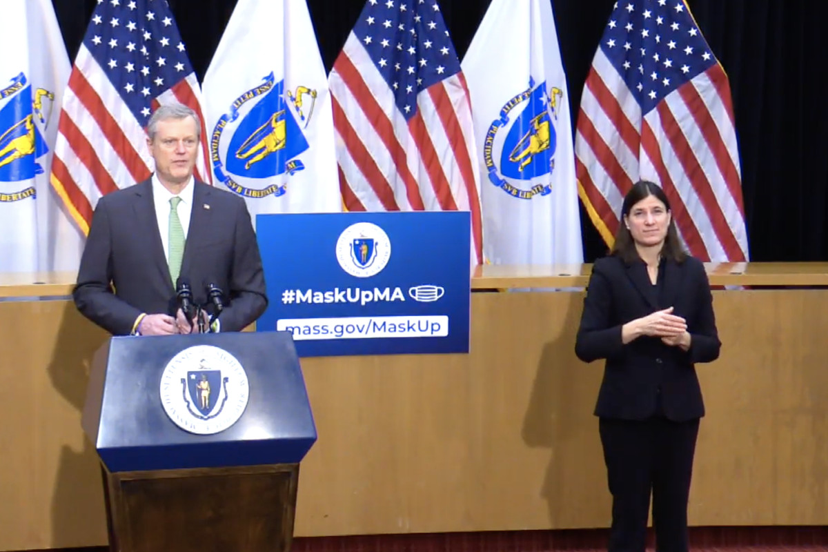 Mass. Governor Charlie Baker stands in front of a podium, adjacent an ASL translator, backdropped by American and Massachusetts flags