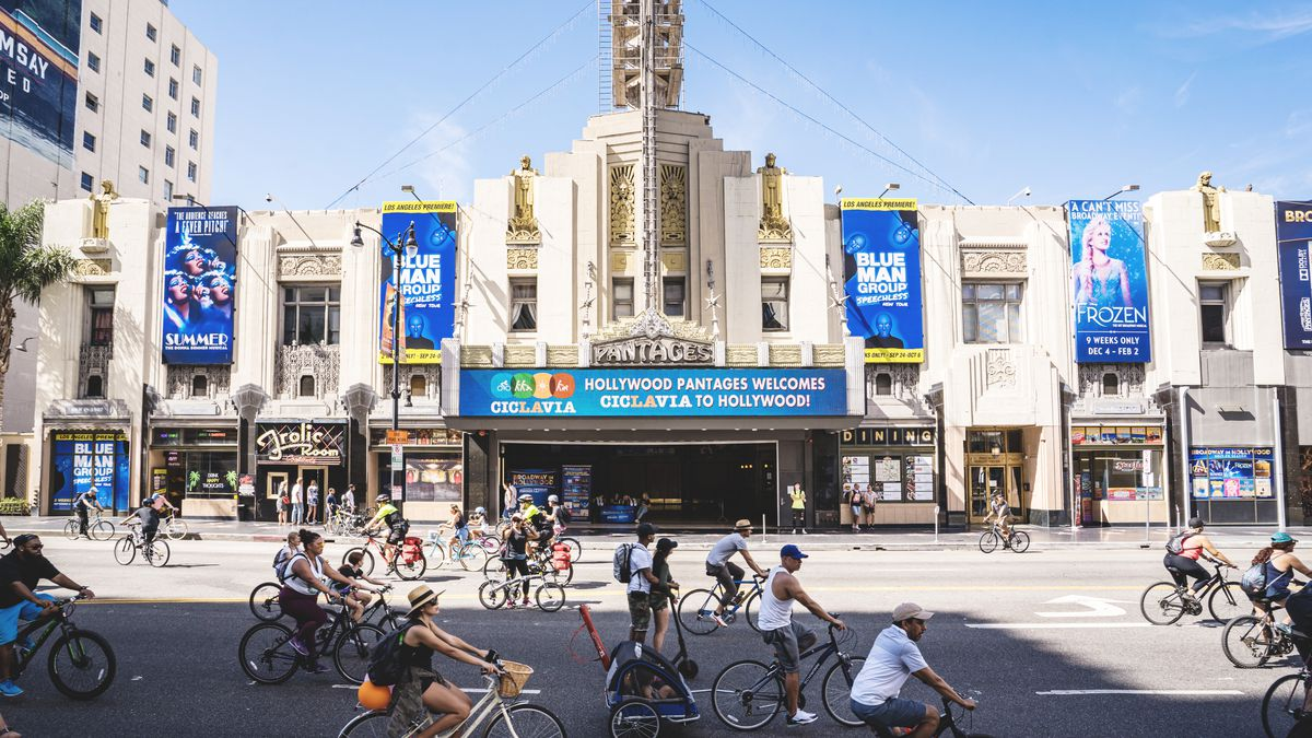 People ride bikes and walk in the street in front of an ornate theater as part of an open streets event in Hollywood.