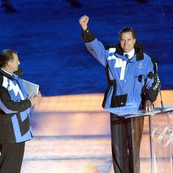 Mitt Romney gestures to the crowd during the opening ceremonies of the Salt Lake 2002 Winter Olympic Games at Rice-Eccles Stadium Friday, Feb. 8, 2002.