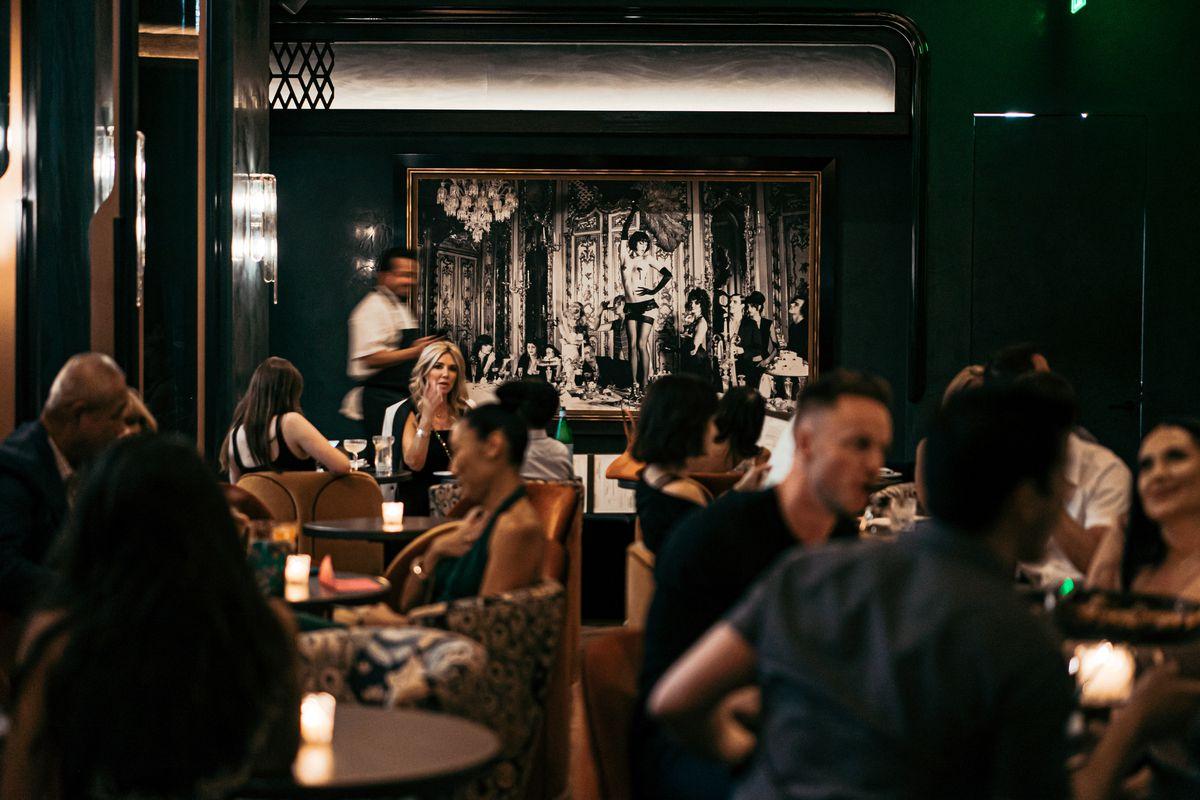 Habitación llena de gente hablando dentro de un salón con paredes con paneles de madera
