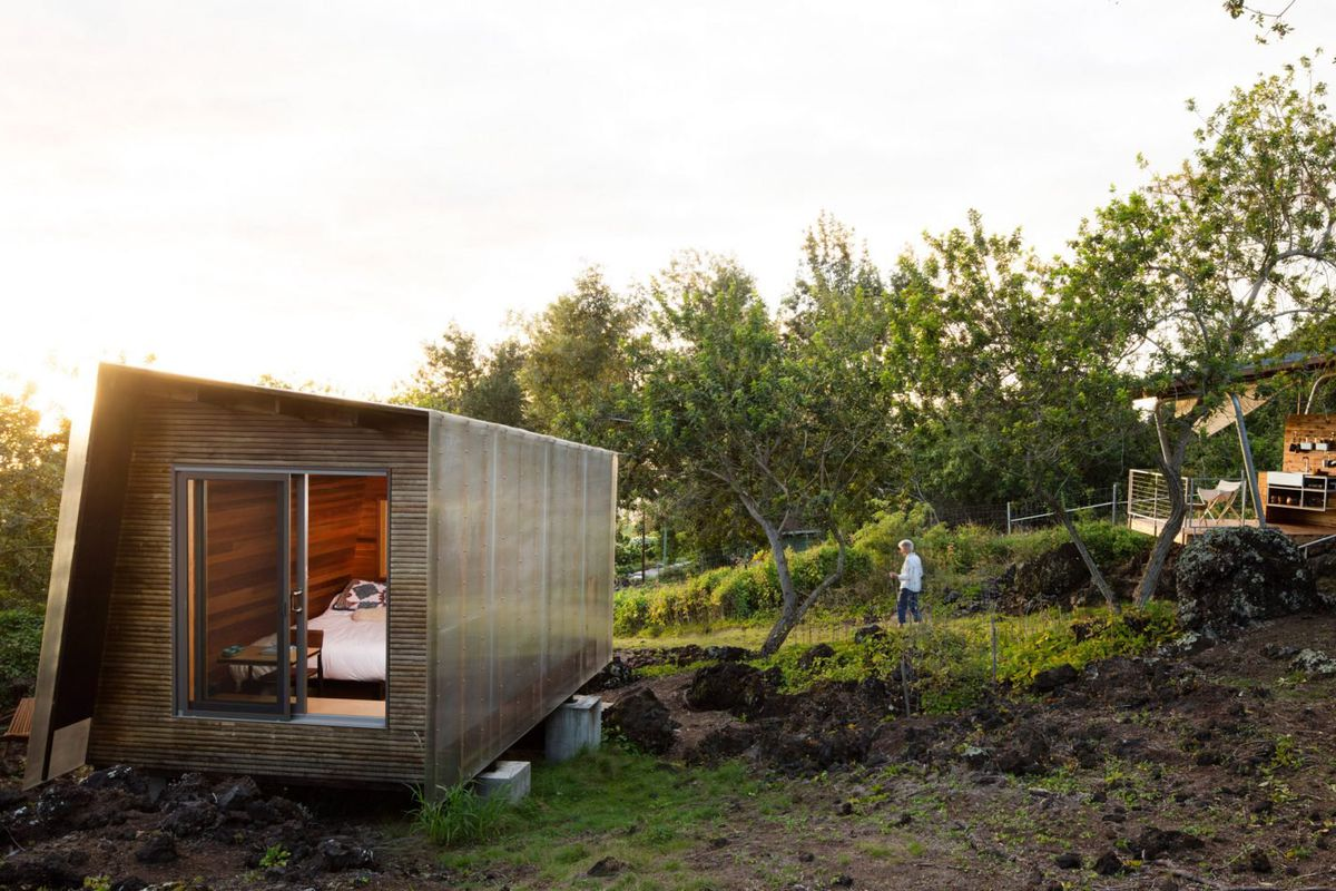 A tiny wood-and-polycarbonate structure and a pavilion with outdoor kitchen occupy a rugged spot outdoors.