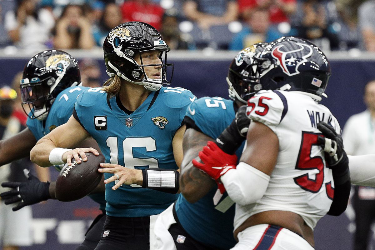 Trevor Lawrence #16 of the Jacksonville Jaguars delivers a pass in the pocket as he receives pressure from DeMarcus Walker #55 of the Houston Texans at NRG Stadium on September 12, 2021 in Houston, Texas.