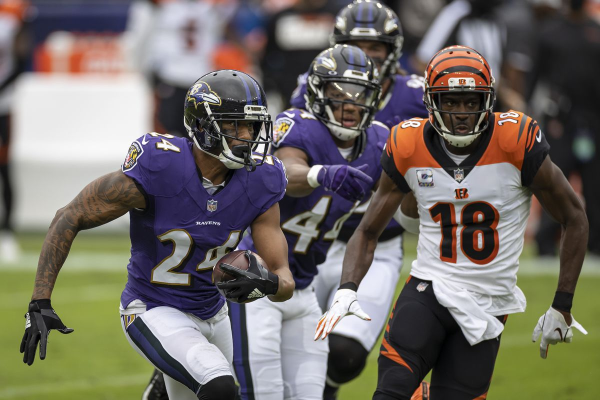 Marcus Peters #24 of the Baltimore Ravens returns an interception as A.J. Green #18 of the Cincinnati Bengals pursues during the first half at M&T Bank Stadium on October 11, 2020 in Baltimore, Maryland.