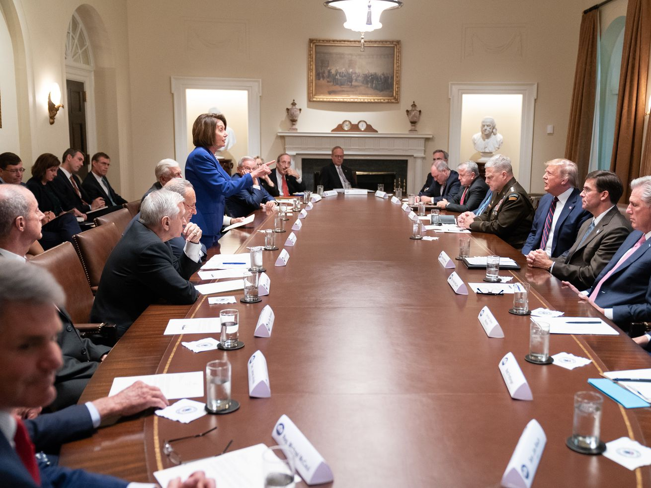 House Speaker Nancy Pelosi stands up and speaks to President Trump, pointing at him, as he and other men sit around a long table at a White House meeting.
