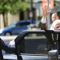 Former President Bill Clinton waves to people on the street as he arrives for a roundtable meeting with business leaders at the One Utah Center in Salt Lake City on Thursday, Aug. 11, 2016.