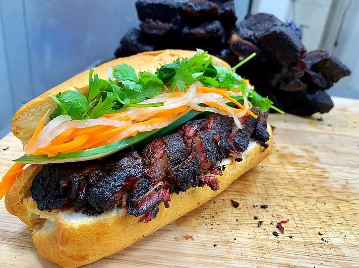 A banh mi filled with charred beef, carrots, white onions, and cilantro sits on a wood slab.
