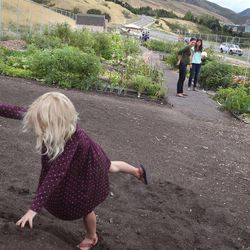 Lily Munson, 4, plays in a pile of dirt while her mother, Maryann, and Lisa Boone chat after the dedication of the Popperton Plots community garden in Salt Lake City on Friday, Aug. 22, 2014.