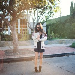 """Rumi of <a href=""""http://www.fashiontoast.com""""target=""""_blank""""> Fashion Toast</a> is wearing an Isabel Marant x H&M cardigan, a Reformation dress, Theory boots and a 3.1 Phillip Lim clutch."""
