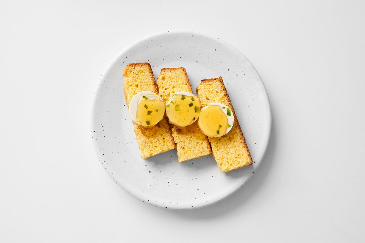 Three yellow pieces of cornbread with a drizzle of syrup on top