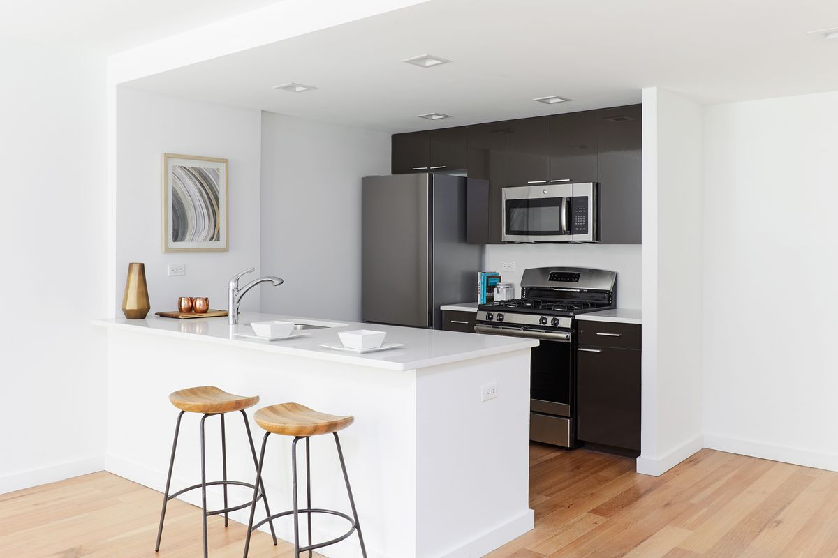 A kitchen with an island, two high top chairs, and dark brown cabinetry.