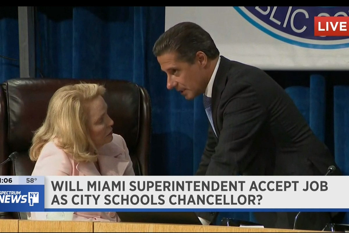Cavalho talks to Miami's school board chair during a break in the meeting Thursday.