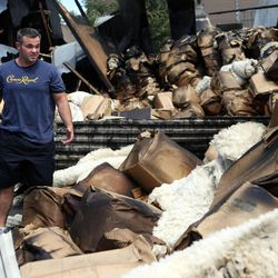Shane Wimmer checks out the damage after an early morning fire destroyed 22 storage units in Millcreek on Friday, July 27, 2012. Wimmer's storage unit was spared.