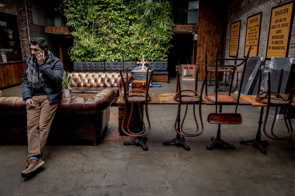 A man takes a phone call in a cafe that has been barricaded so nobody sits