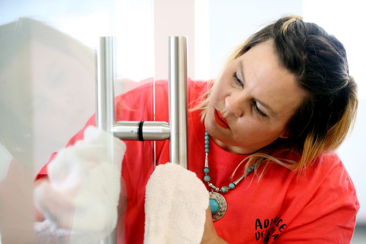 Nikki Line, owner of Advanced Deep Clean, dries a door handle in an office in a new building in Farmington on Tuesday, March 17, 2020.