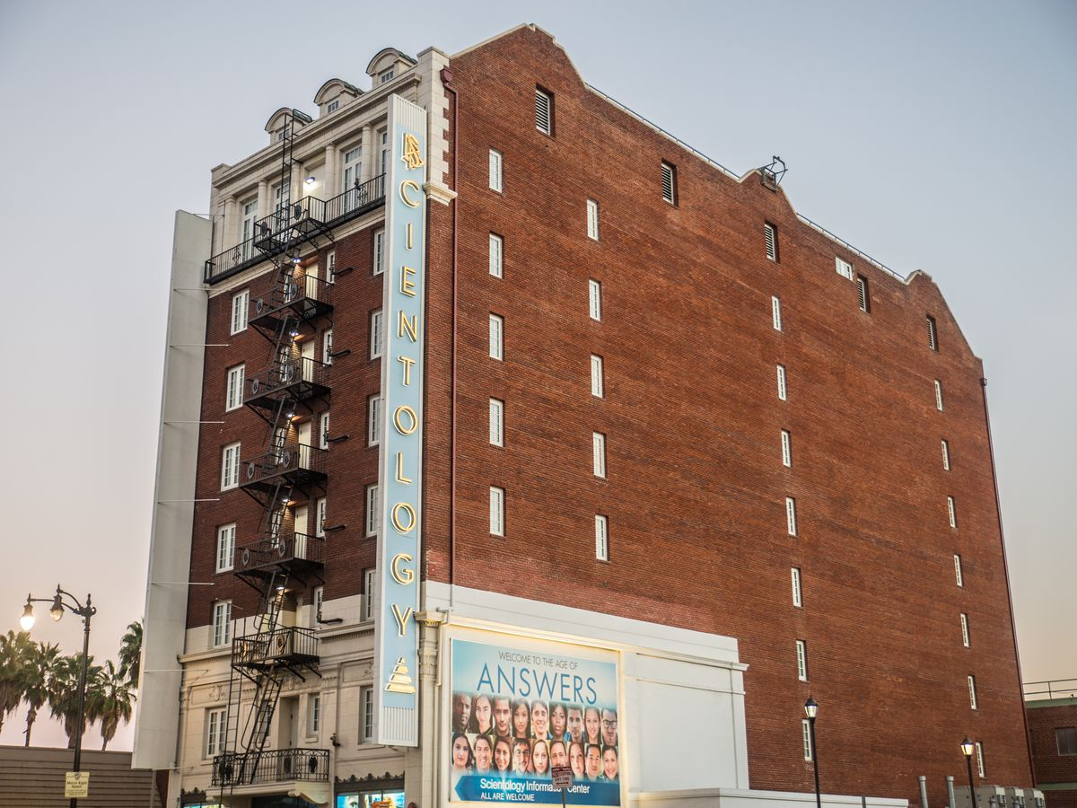 The exterior of the former Christie hotel. The facade is red brick and there is a sign on the front of the building that reads: scientology.