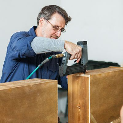 Man Attaches Internal Sides Of Dresser With Wood Glue And Pneumatic Nail Gun For Bathroom Vanity