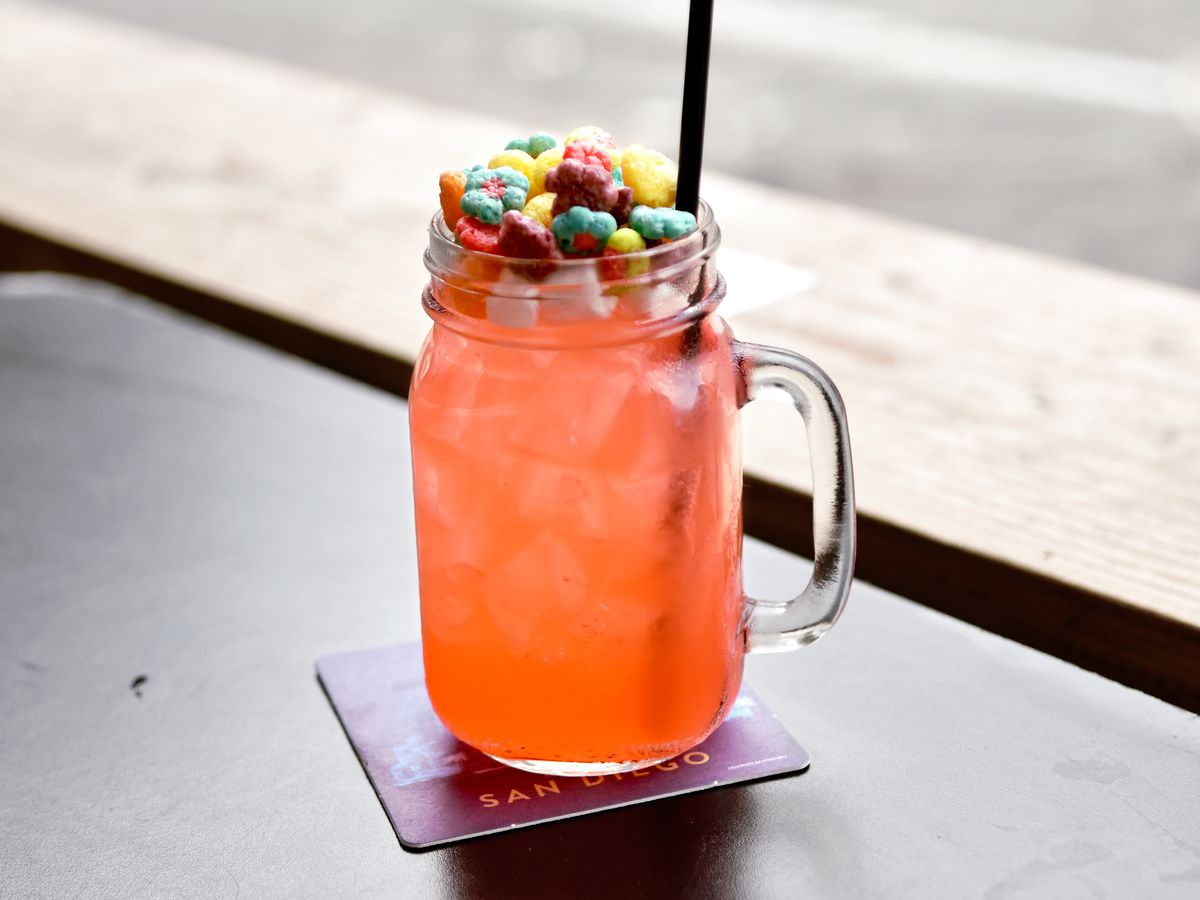 Pink cocktail with marshmallows and Trix cereal on top.