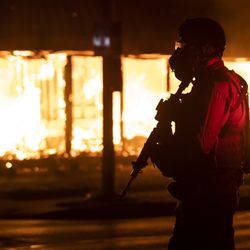 A member of the Wisconsin National Guard stands watch outside B&L Office Furniture Inc. at 1101 60th St. in Kenosha, one of several businesses to burn during the second night of unrest after police shot Jacob Blake, Monday night, Aug. 24, 2020.