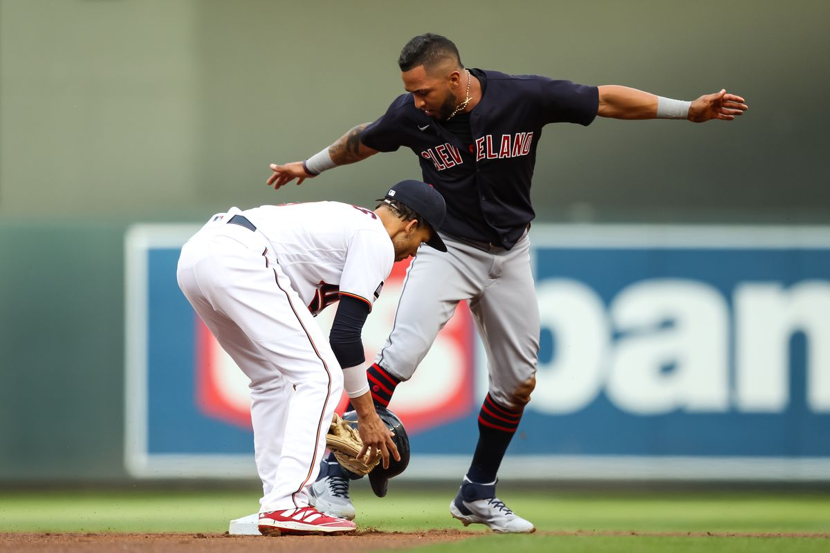 Andrelton Simmons of the Minnesota Twins fields a ball as Eddie Rosario #9 of the Cleveland Indians steals second base in the first inning of the game at Target Field on June 25, 2021 in Minneapolis, Minnesota. The Twins defeated the Indians 8-7.