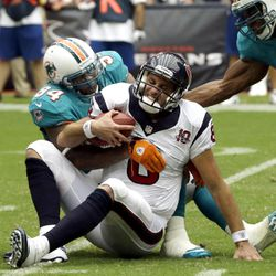 Houston Texans quarterback Matt Schaub (8) is sacked by Miami Dolphins defensive tackle Randy Starks (94) and linebacker Cameron Wake, right, in the second quarter of an NFL football game, Sunday, Sept. 9, 2012, in Houston.