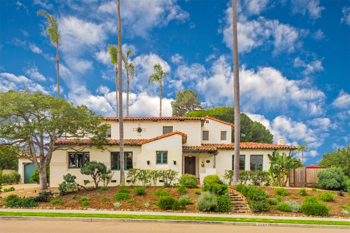 Two-story Spanish-style home with clay roof tiles and palm trees surrounding it.