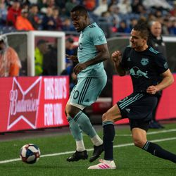 FOXBOROUGH, MA - APRIL 20: New York Red Bulls defender Aaron Long #33 makes a tackle on New England Revolution forward Cristian Penilla #70 during the second half at Gillette Stadium on April 20, 2019 in Foxborough, Massachusetts. (Photo by J. Alexander Dolan - The Bent Musket)