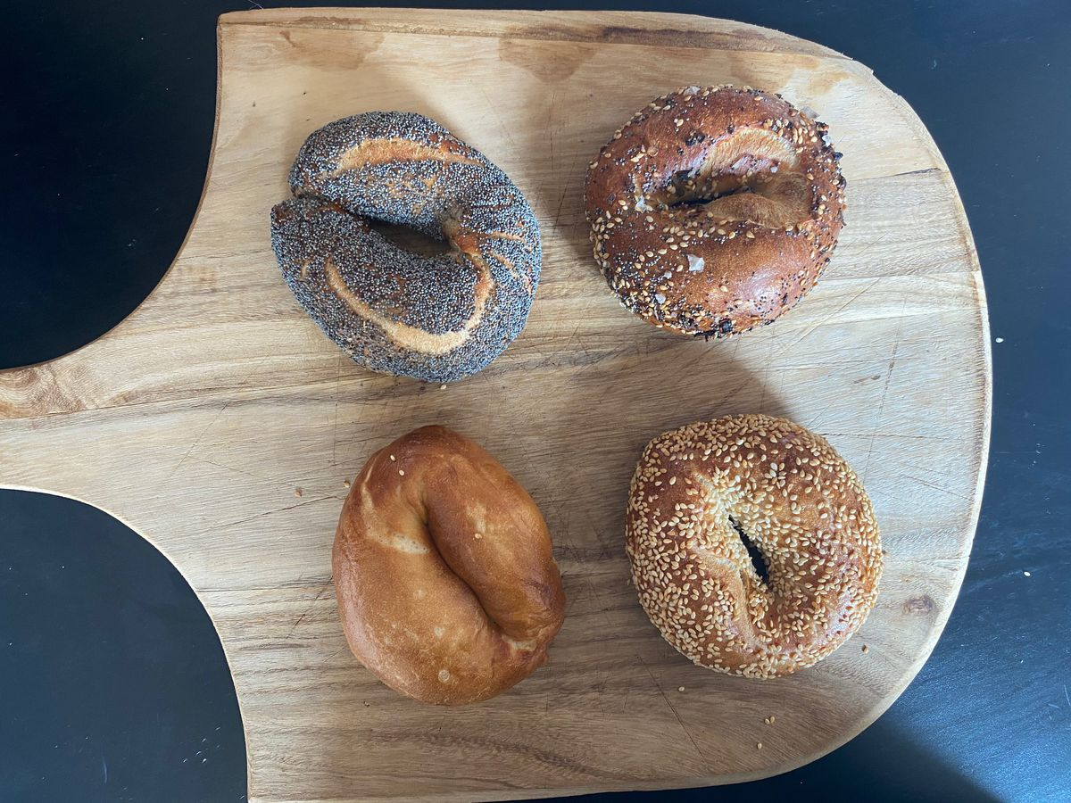 Four bagels (poppy, everything, sesame, plain) on a wooden pizza peel